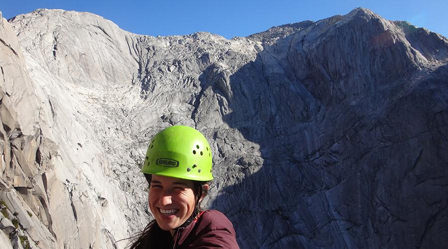 Woman smiling while rock climbing