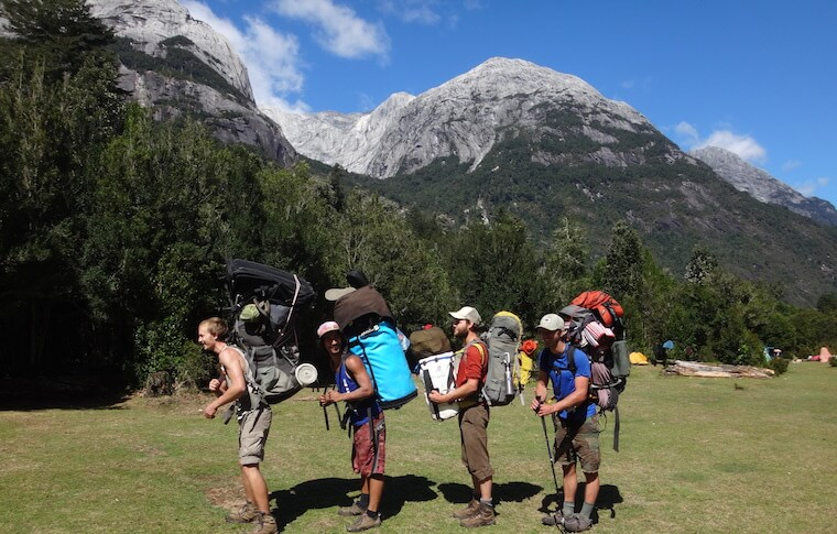 Four backpackers in front of trees and mountains