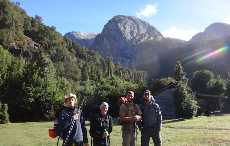 Four hikers in front of a cabin and a mountain