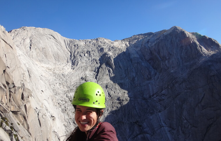 A girl in a helmet on the mountain top