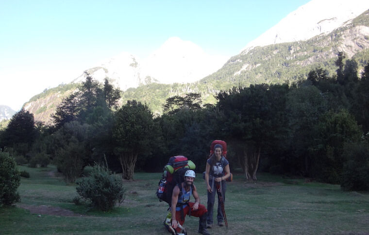 Two hikers in the forest in front of a mountain