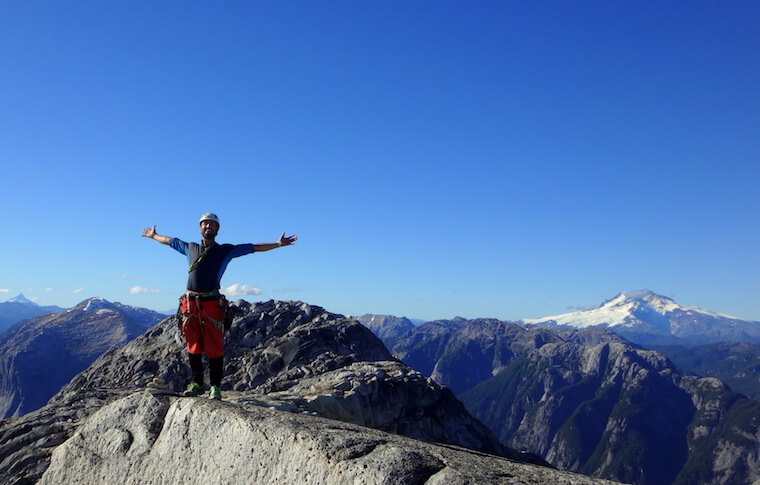 A man with his arms open on the mountain top