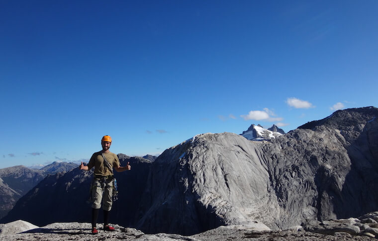 A man in a helmet with his thumbs up on the mountain top