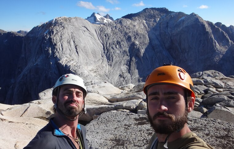 Two men in helmets on the mountain top