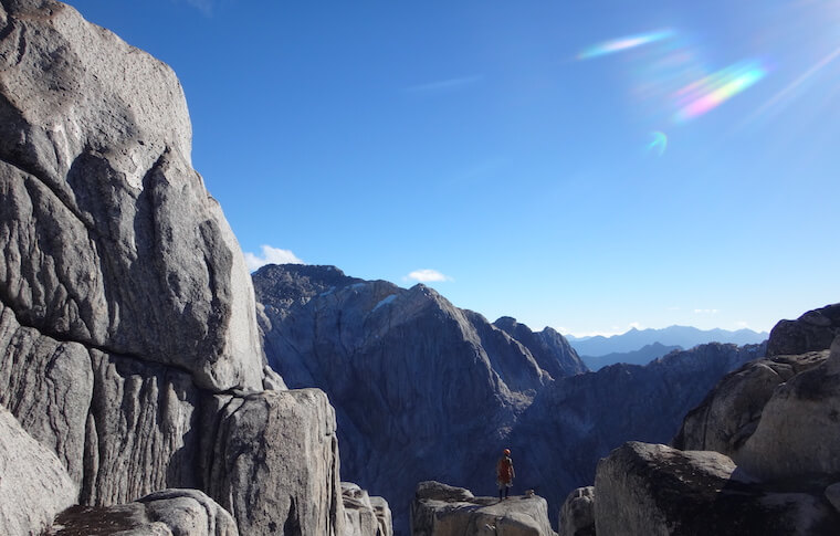 A person on top of a rock in a mountainous landscape