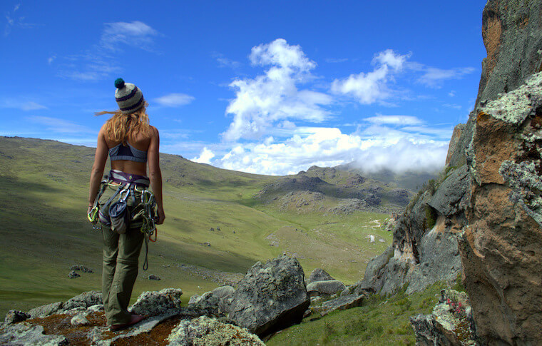 A woman looking over a green valley between mountains