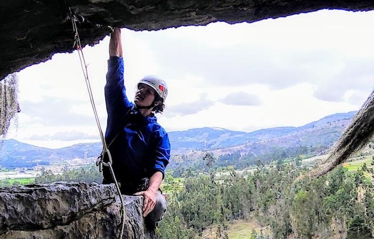 A climber outside a cave