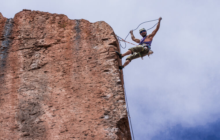 Climber hanging off the top of a rock