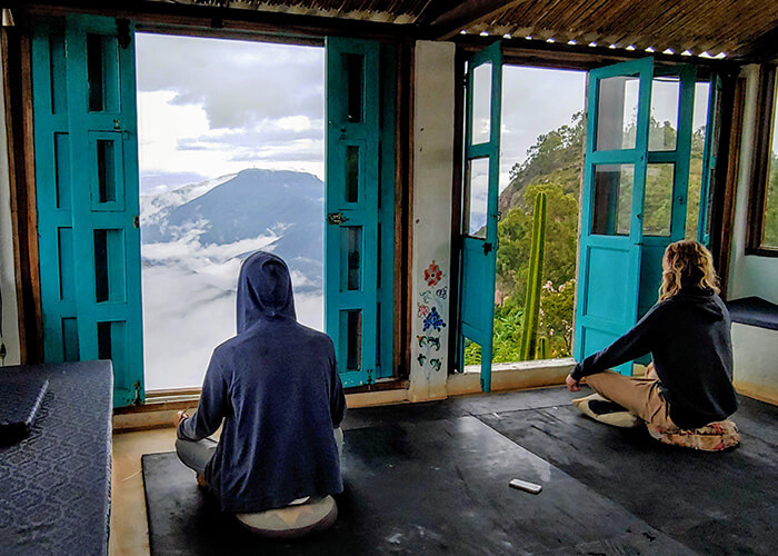 People meditating in a traditional house between the Colombian mountains