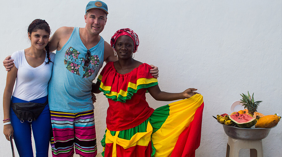 Tourists posing with a Colombian woman dressed in the traditional costume