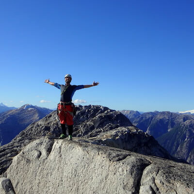 A man standing on the mountain top with his arms wide open