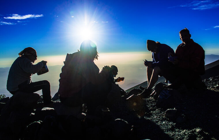 Five tourists resting on the mountain top