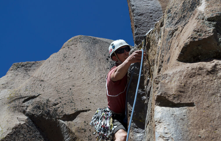 A man with equipment climbing a rock