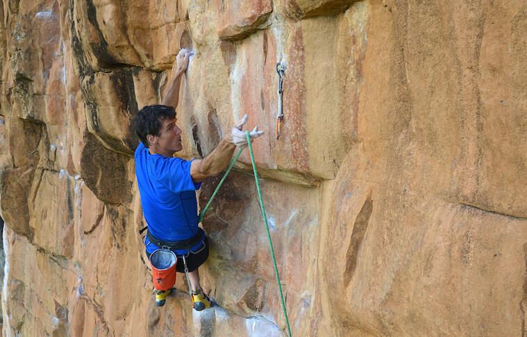 A man in a blue T-shirt climbing a rock