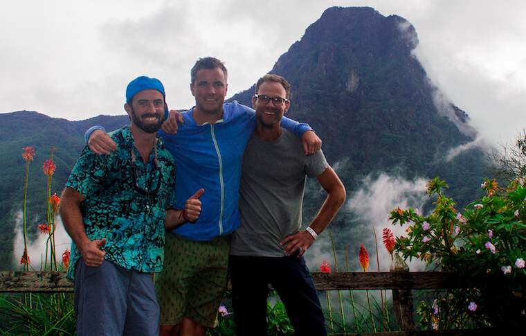 Three tourists smiling in front of a mountain and flowers
