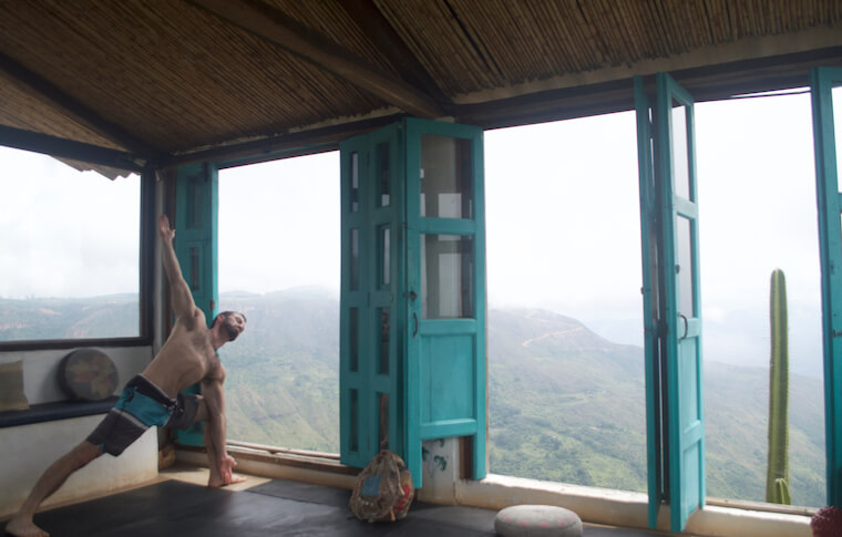A man doing yoga in front of open windows