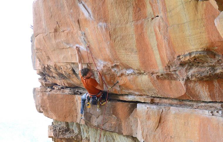 A rock climber clinging to a rock
