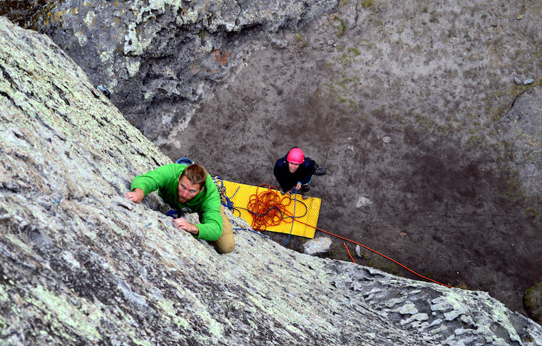 Two people climbing a cliff