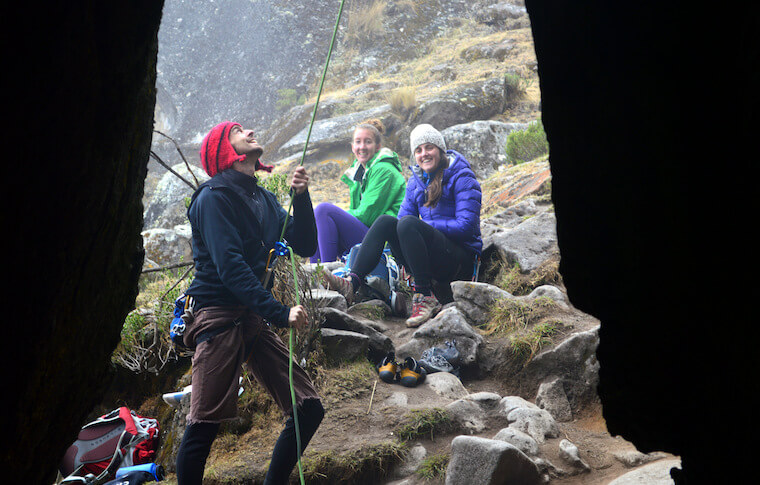 A tourist preparing to climb and two others watching him and smiling