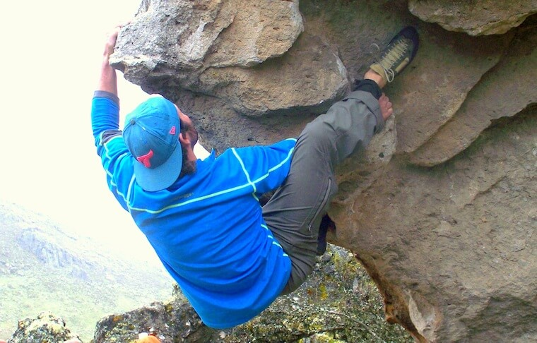 A man climbing a rock with no equipment
