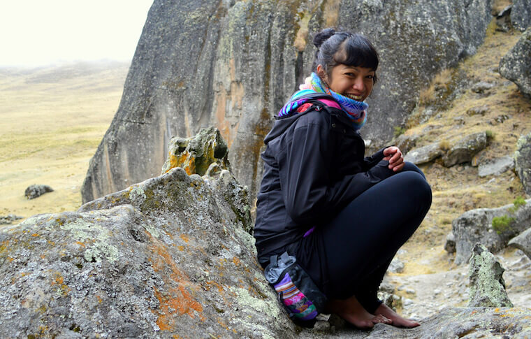 A girl sitting on the mountain and smiling