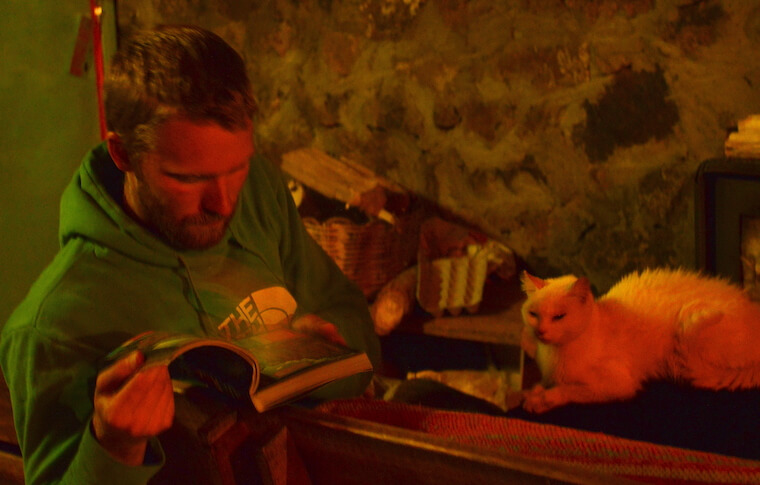 A man reading a book next to a cat in a cabin